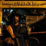 A policeman stands guard outside a Sufi shrine after it was hit by multiple suicide blasts in Karachi