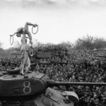 Soldiers Watch Acrobats Perform on Tank