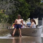 A man sits in the front of his boat as he navigates through floodwaters in Depot Hill in Rockhampton