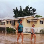 Women walk through floodwaters at Depot hill in Rockhampton