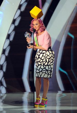 One of the four outfits worn by Katy Perry featured a big bright cube on her head, as if her thoughts were controlled by it. In fact, it reminded me of the icon you see when selecting a player to control in the Sims video game.