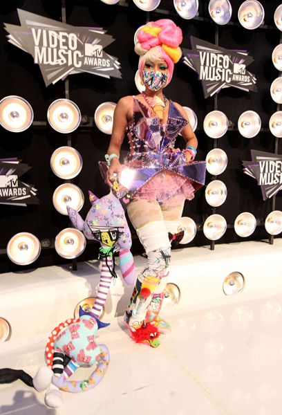 "During the 2011 VMAs, Nicki wore a Harajuku-inspired dress featuring mirror fragments (a Monarch symbol representing the fragmenting of personality). The combination of ""kiddie"" accessories with the sexiness of the dress' cut (it's ""revealing"" at the right places) is a little questionable."