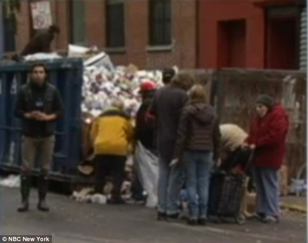 Shocking images show desperate New Yorkers digging through dumpsters for food as downtown Manhattan embarks on fourth night without power