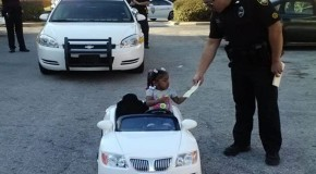 Aren't you a little young to be behind the wheel? Adorable moment that toddler is 'pulled over' by police in her toy convertible and given a $4 ticket for reckless driving